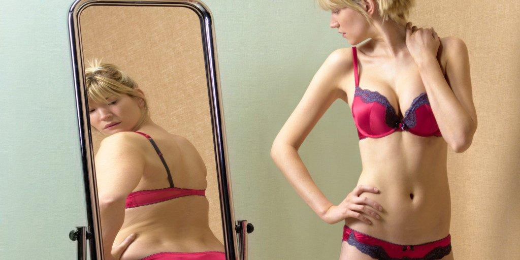Девушка видит себя в зеркале толще, чем на самом деле