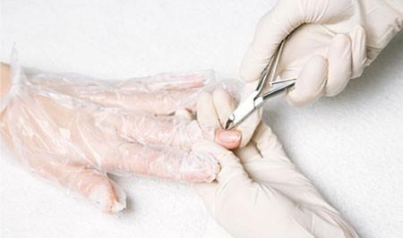 Процесс обрезания кутикулы специальными щипчиками