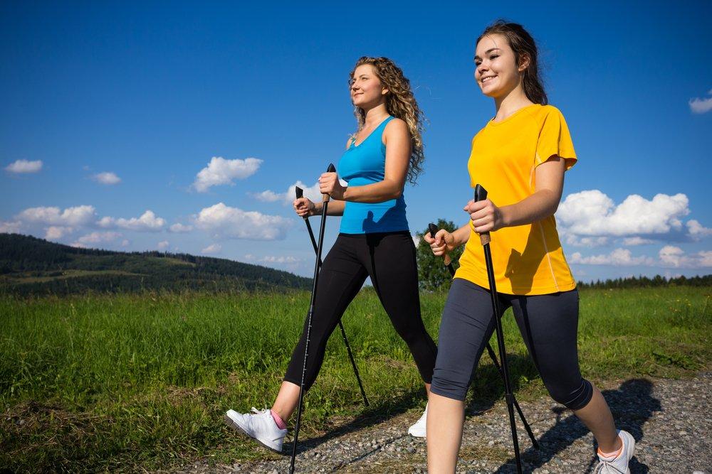 Две девушки занимаются скандинавской ходьбой