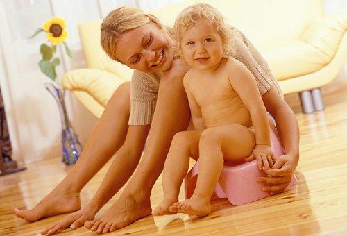 Мама обнимает девочку, сидящую на розовом горшке